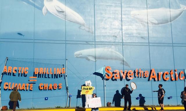 """Extracción en el Ártico igual caos climático, asegura una gran pancarta en la ciudad de Anchorage, en Alaska, que reclama """"Salvemos el Ártico"""", en una demanda de activistas a los participantes en la conferencia Glacier sobre el Ártico, promovida por el Departamento de Estado de Estados Unidos. Crédito: Leehi Yona/IPS"""