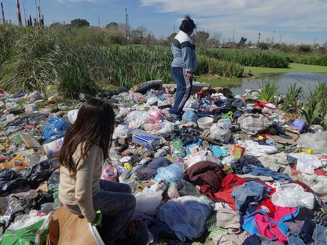 Nora Pavón y una de sus hijas, en la parte trasera de su casa, con el basural y el pantano circundante, una cloaca natural en Villa Inflamable, en el municipio de Avellaneda, en el sur de la capital de Argentina. Crédito: Fabiana Frayssinet/IPS