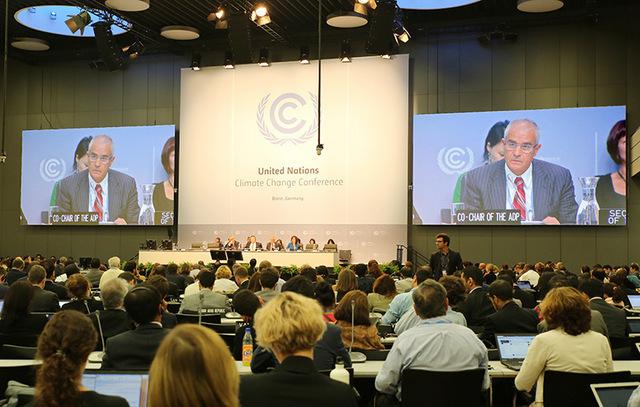 En las pantallas del plenario de la sesión de negociaciones climáticas de Bonn, la imagen del copresidente del ADP, el argelino Ahmed Djoghlaf, durante la clausura. Crédito: Cortesía de IISD