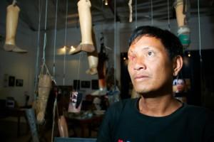 Ta Doangchom, víctima de una bomba de racimo, al lado de las prótesis caseras del Centro Nacional de Rehabilitación – Empresa Cooperativa de Ortopedia y Prótesis, en Vientiane, Laos. Crédito: Irwin Loy/IPS