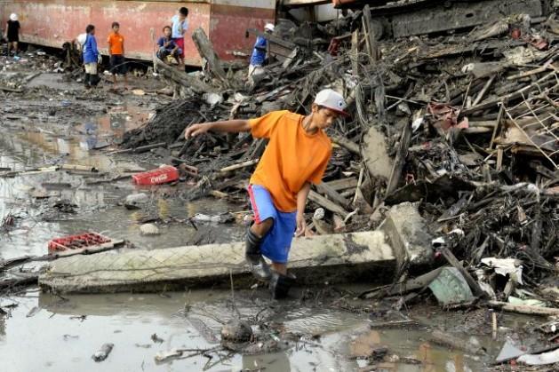 Un joven de la ciudad de Tacloban, en Filipinas, en medio de la destrucción que dejó a su paso el tifón Yolanda, el 21 de diciembre de 2013. Crédito: Evan Schneider/ONU