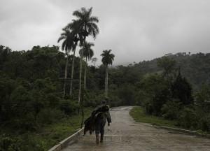 Un hombre transita por un camino cuesta arriba en el municipio montañoso de Victorino, en la provincia de Granma, en Cuba, en un día lluvioso. Crédito: Jorge Luis Baños/IPS