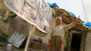 Rinaz Rojelat, el único comerciante que queda en la aldea de Zergely, en las montañas de Qandil, en el Kurdistán iraquí. Su negocio está justo frente a las ruinas de las casas destruidas de sus vecinos por el bombardeo de la aviación turca en agosto de este año. Crédito: Karlos Zurutuza/IPS