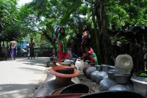 Decenas de mujeres esperan en fila para llenar cientos de recipientes con agua en Bangladesh. Crédito: Amantha Perera / IPS
