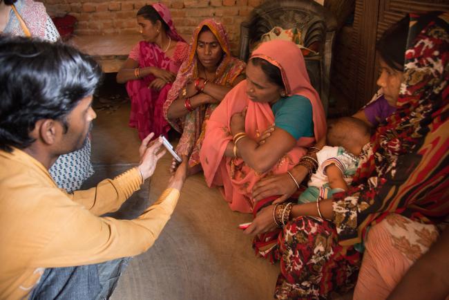 Un agente muestra a las beneficiarias de Grameen cómo hacer transacciones con el teléfono móvil. Crédito: Cortesía Banco Grameen..