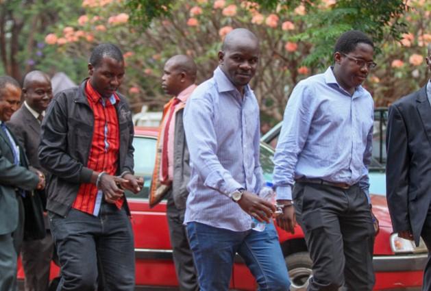 Periodistas del semanario Sunday Mail son trasladados al tribunal en Zimbabwe. La imagen muestra, de izquierda a derecha, a Tinashe Farawo, Brian Chitemba y Mabasa Sasa. Crédito: Jeffrey Moyo / IPS.