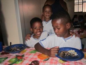 Gracias a la alianza con los agricultores familiares locales, en los menús de las escuelas públicas de Brasil, donde se educan 45 millones de niñas y niños, predominan vegetales y frutas, creando hábitos alimentarios saludables. Tres alumnos de la Escuela Municipal João Baptista Cáffaro, en la ciudad brasileña de Itaboraí, bromean durante el almuerzo del 6 de noviembre de 2015. Crédito: Mario Osava/IPS