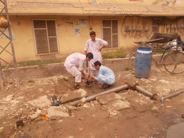 Jóvenes aprovechan el agua de una tubería con fugas en la ciudad paquistaní de Peshawar. Crédito: Ashfaq Yusufzai / IPS
