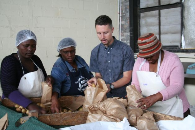 Christopher D'Aiuto, especialista en suelos y coordinador de producción de Harvest of Hope ayuda a un grupo de mujeres de la organización Abalimi Bezekhaya a preparar los paquetes con verduras frescas. Crédito: Astrid Stark/IPS.