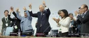 Líderes de la cumbre aplauden y hacen señales de victoria al lograrse el histórico Acuerdo de París.