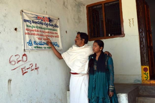 El sacerdote hindú Shri Kumar Sharma y su hija Bhargavi leen un cartel contra el matrimonio infantil que dice que toda persona hallada culpable de estar involucrada en una boda de una menor será castigada con dos años de cárcel y una multa de 100.000 rupias (unos 1.470 dólares). Crédito: Stella Paul/IPS.