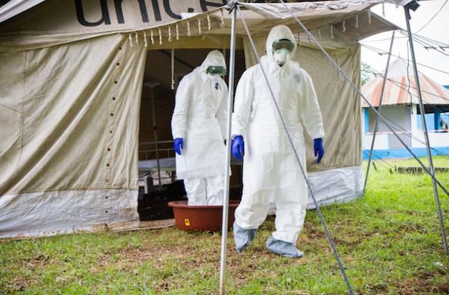 Dos trabajadores de la salud ponen los pies en un recipiente de agua con hipoclorito de sodio, a la salida de una tienda de campaña en aislamiento durante un simulacro de atención a pacientes con ébola en el hospital de Biankouman, en Costa de Marfil, en agosto de 2014 . Crédito: Marc-André Boisvert/IPS