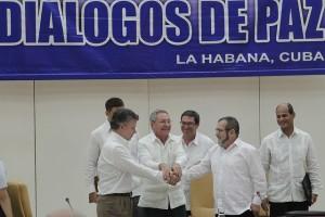 El presidente cubano Raúl Castro (centro), estrecha las manos del presidente colombiano Juan Manuel Santos (izquierda) y del líder de las FARC, Rodrigo Londoño,el 23 de septiembre, en La Habana. Un histórico momento en que las dos partes pactaron tener un Acuerdo Final para la paz en Colombia el 23 de marzo, un compromiso que no pudo cumplirse. Crédito: Jorge Luis Baños/IPS