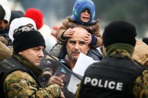 Un padre desesperado, con su hijo llorando sobre los hombros, que sobreviven en condiciones insoportables en el campamento de Indomeni, en la frontera de Grecia con Macedonia, trata sin éxito de que gendarmes de ese país le permitan el paso para adentrarse en Europa. Crédito: Dimitris Tosidi/IRIN