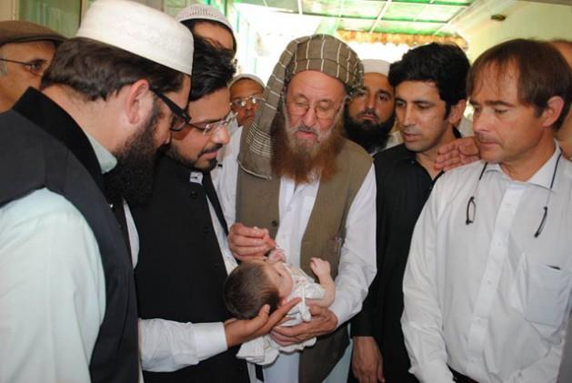 El conocido religioso Maulana Samiul Haq administra la vacuna contra la poliomielitis a un bebé en Pakistán. Crédito: Ashfaq Yusufzai/IPS.