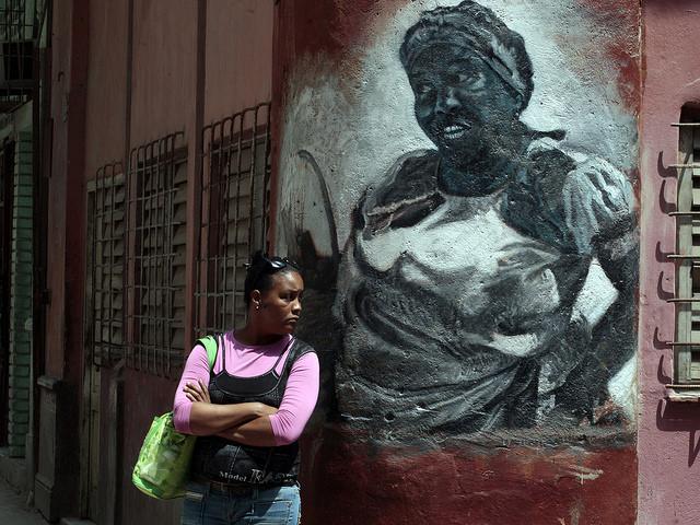 Una mujer permanece junto a un grafiti pintado en la pared de una vivienda, que muestra la imagen de una afrodescendiente, en La Habana Vieja, en la capital de Cuba. Crédito: Jorge Luis Baños/IPS