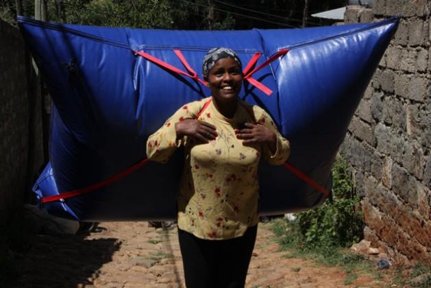 Salome Zeresulos carga una mochila de (B)energy con biogás en la capital de Etiopía. Crédito: James Jeffrey/IPS.