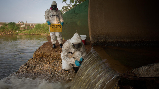 Dos técnicos de Greenpeace toman muestras de las aguas del río que colinda con el Complejo Petroquímico de Pajaritos, en la ciudad mexicana de Coatzacoalcos, donde el 20 de abril estalló la Planta Clorados III, en un incidente que dejó 32 personas muertas y 136 heridas. Crédito: Greenpeace México