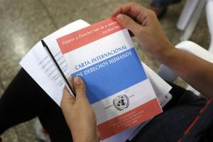 """Una persona sostiene en sus manos un manual impreso de la Carta Internacional de Derechos Humanos durante la sexta edición del taller anual """"Derechos económicos, sociales y culturales y perspectiva de derechos humanos"""", en la ciudad de Cárdenas, en Cuba. Crédito: Jorge Luis Baños/IPS"""