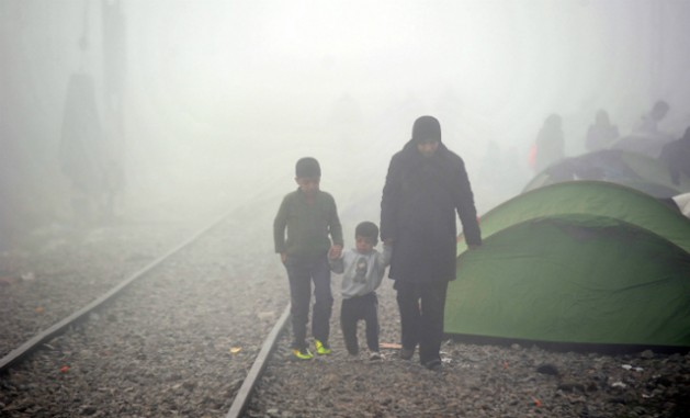 Una mujer camina con sus dos hijos de la mano al costado de las vías del tren en medio de la bruma en Idomeni, Grecia, en marzo de 2016. Crédito: ©UNICEF/UN012794/Georgie.