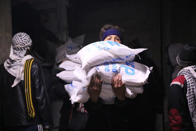 En la ciudad de Madaya, Siria, integrantes de la comunidad ayudan a descargar y distribuir la asistencia humanitaria. Crédito: WFP/Hussam Al Saleh.
