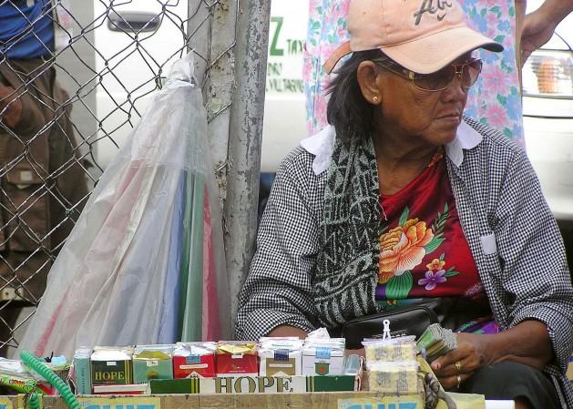 Una vendedora callejera en Manila ofrece paquetes de 20 cigarrillos a menos de un dólar. Crédito:Kara Santos/IPS.