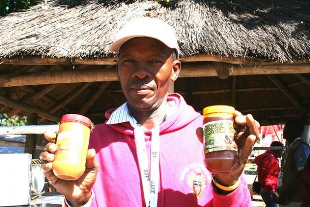 El agricultor y apicultura zimbabuense Nyovane Ndlovu muestra unos frascos de miel producidos con su propia marca. Crédito: Busani Bafana/IPS.