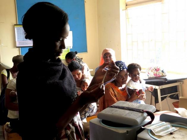 Mujeres esperan para vacunar a sus hijos en el Centro de Salud Kisugu en Kampala, Uganda. La enfermera en primer plano es Betty Makakeeto. Crédito: Amy Fallon/IPS