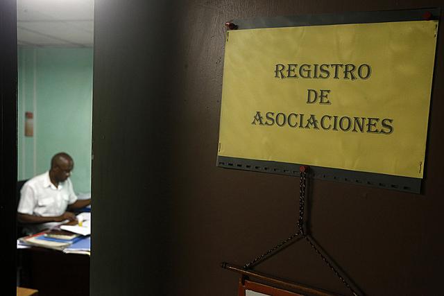 Un funcionario labora con la puerta apenas entreabierta en el departamento de registro de la Dirección de Asociaciones del Ministerio de Justicia, en la capital de Cuba. Los activistas esperan por una reforma legal que abra de par en par las puertas a la regulación de las organizaciones de la sociedad civil en el país. Crédito: Jorge Luis Baños/IPS