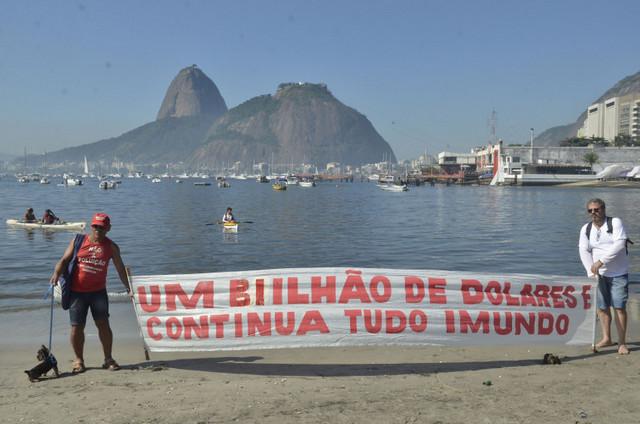 """""""Mil millones de dólares y todo continúa inmundo"""", denuncia una pancarta en la playa de la bahía de Guanabara, en Río de Janeiro, donde se celebrarán varias competencias náuticas de los Juegos Olímpicos y cuya descontaminación ha sido una promesa incumplida. Crédito: Fernando Frazão/Agência Brasil"""