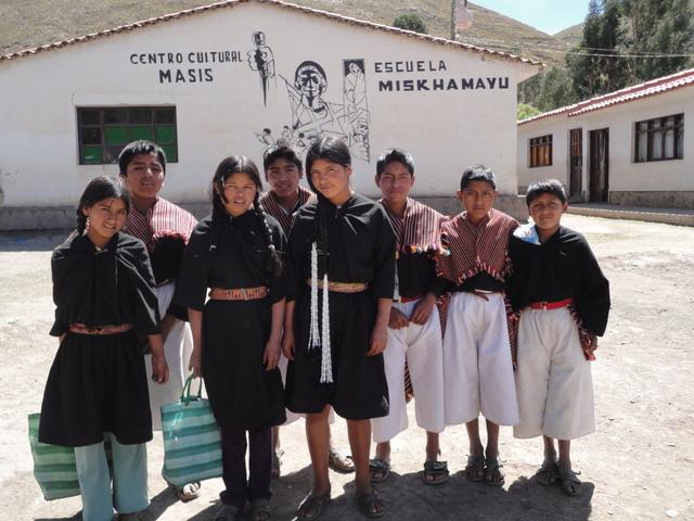 Escolares indígenas ante la Unidad Educativa Miskhamayu, en una aislada región de los Andes bolivianos. Muchos alumnos llegan tras recorrer diariamente más de 12 kilómetros por su accidentada orografía desde sus comunidades, para repetir el trayecto al concluir las clases. Crédito: Marisabel Bellido/IPS