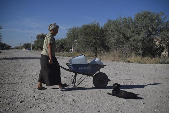 En medio del sol que golpea al pueblo de La Sierrita, una pobladora acarrea unas garrafas de agua para abastecer a su familia. Crédito: José Ignacio de Alba y Mónica González/Pie de Página