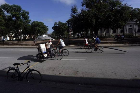 Un transeúnte carga con recipientes de agua en una especie de sidecar acoplado a su bicicleta en la ciudad de Holguín, en el oriente de Cuba. Los habitantes de la urbe tratan de acceder a la escasa agua por las vías disponibles a su alcance. Crédito: Jorge Luis Baños/IPS