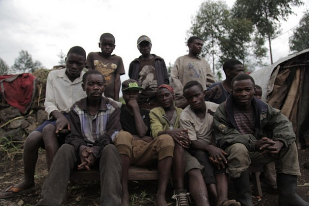 Un grupo de jóvenes bambutis de Biganiro, RDC, sentados frente a sus casas, estructuras provisionales hechas de madera y láminas de plástico. Crédito: Zahra Moloo / IPS