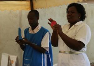 Personal de la salud enseña a un grupo de mujeres cómo se usa un condón, en la clínica Christa en Jinja, Uganda. Crédito: Lyndal Rowlands/IPS.