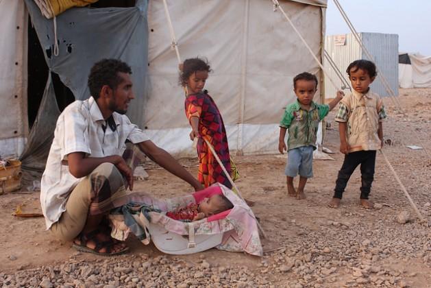 Un hombre yemení cuida a un bebé en el campamento de Obock. Crédito: James Jeffrey / IPS