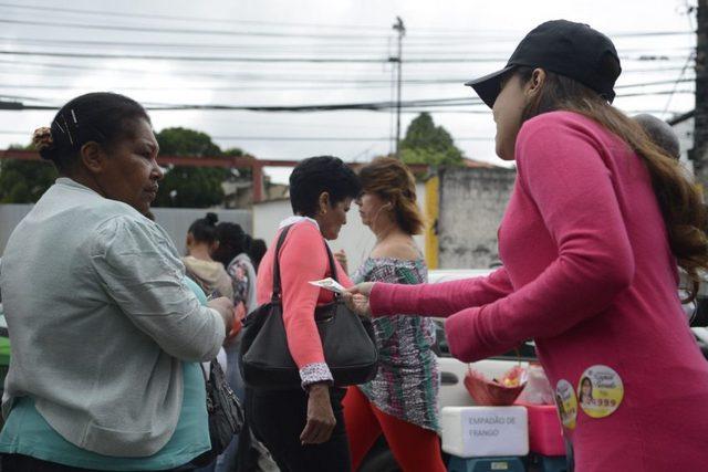 Una joven activista entrega propaganda a una mujer durante la primera vuelta de las elecciones municipales del 2 de octubre, en Brasil. Crédito: Tânia Rêgo/Agência Brasil