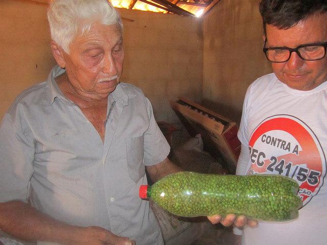 Raimundo Pinheiro de Melo, un campesino de 76 años del municipio de Apodi, en el Nordeste de Brasil, más conocido cono Mundinho, muestra a un agricultor que lo visita una botella con semillas de frijoles que custodia. Crédito: Mario Osava/IPS