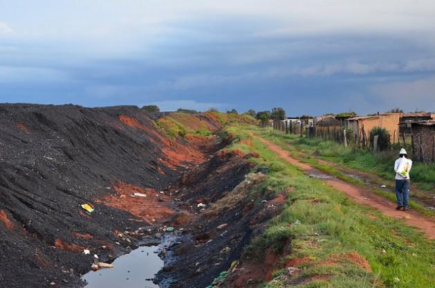 La aldea de Masakane, en Mpumalanga, se ubica apenas a unos metros de pilas de carbón que alimentan la estación de generación eléctrica Duvha. La industria formal de carbón no generó las oportunidades económicas previstas, lo que llevó a muchas personas a dedicarse a pequeñas actividades de extracción para generar ingresos. Crédito: Mark Olalde/IPS.