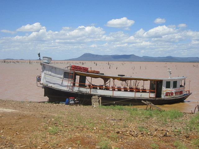 Un barco en reparación en la orilla del embalse de Sobradinho, con bajo nivel de agua por los cinco años de sequía que atormenta al interior semiárido del Nordeste de Brasil. Se entrevén arbustos sumergidos por las aguas represadas del río São Francisco desde los años 70. Crédito: Mario Osava/IPS