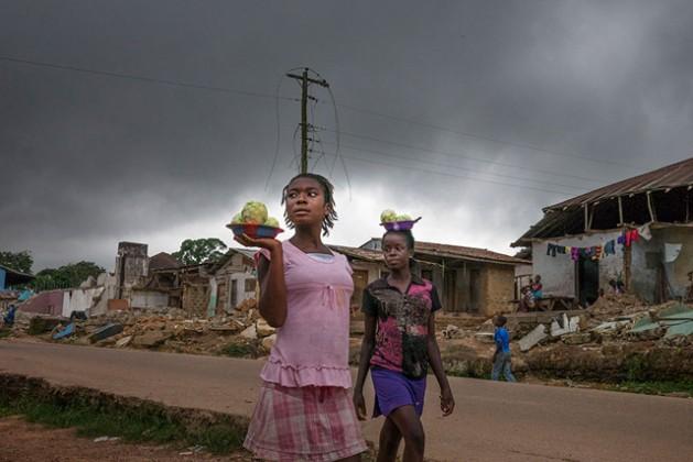 La infraestructura de Liberia fue destruida durante la guerra civil (1989-2003). Unas niñas caminan en el pueblo de Totota, en el condado de Bong, mirando las vivendas demolidas por las autoridades para reconstruir las calles. Crédito: ONU Mujeres.