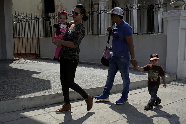 Una familia cubana transita por una céntrica calle del barrio de Vedado, en La Habana, en Cuba, en el municipio Plaza de La Revolución, en La Habana, en Cuba, donde solo 49 por ciento de los hijos crece en hogares con los dos padres. Crédito: Jorge Luis Baños/IPS