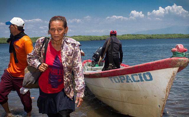 Rosa Herrera retorna a la playa tras pasar la mañana recolectando moluscos en los manglares que bordean Isla de Méndez, en la Bahía de Jiquilisco, en el oriental departamento de Usulután. La lucha por la obtención de alimentos es intensa en estas comunidades pesqueras de El Salvador. Crédito: Edgardo Ayala/IPS