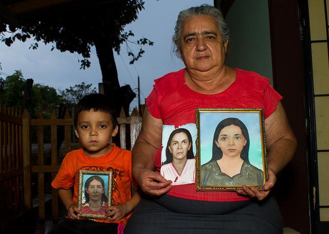 Sofía Romero Pineda, de 55 años, muestra junto a su nieto los pocos retratos que conserva de algunos de los parientes asesinados durante el operativo militar que acabó con la vida de unos 1.000 habitantes de El Mozote y otras aldeas vecinas, en el oriente de El Salvador. Los retratos corresponden a Simeona Vigil, su abuela; Florentina Pereria, su madre, y María Nelly Romero, su hermana. Crédito: Edgardo Ayala/IPS