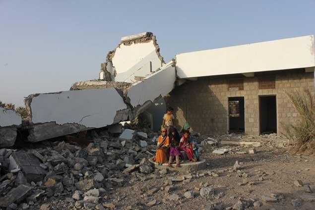 Niñas y niños sentados frente a una escuela muy dañada por el conflicto que sufre Yemen. Crédito: Abu Monassar/UNICEF.