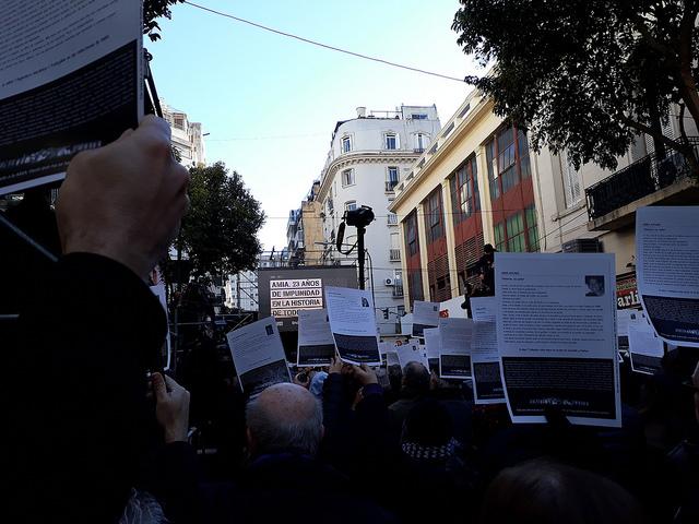 Familiares de las 85 víctimas mortales del atentado contra la AMIA, en la capital de Argentina, exhiben carteles con fotos y datos de sus deudos, durante el acto de conmemoración el 28 de julio, del 23 aniversario del ataque, frente a la nueva sede de la mutual judía en Buenos Aires. Crédito: Daniel Gutman/IPS