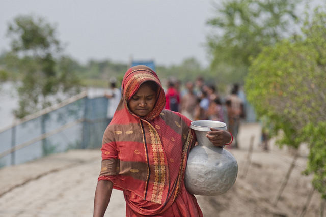 Una mujer carga con un recipiente lleno de agua para beber en el área costera de Bangladesh. Crédito: Rafiqul Islam/IPS.