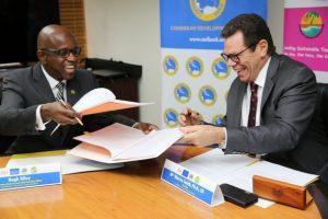 El secretario general de la CTO, Hugh Riley (a la izquierda) y el presidente del Banco de Desarrollo del Caribe, Warren Smith, durante la firma de un acuerdo de asociación. Crédito: Desmond Brown / IPS