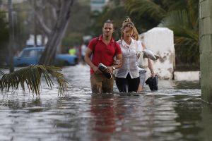 Tres personas transitan con el agua por las rodillas por una céntrica calle inundada en enero de 2017 por la penetración del mar, en el barrio del Vedado, en La Habana, la capital de Cuba, con una creciente vulnerabilidad ante los efectos del cambio climático. Crédito: Jorge Luis Baños/IPS