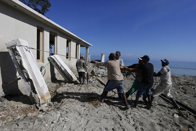 Trabajadores recuperan los muros derribados de una vivienda en construcción en las inmediaciones de la playa de Guanabo, que resultó severamente afectada por las penetraciones del mar al paso del huracán Irma, en el municipio de Habana del Este de la capital de Cuba. Crédito: Jorge Luis Baños/IPS